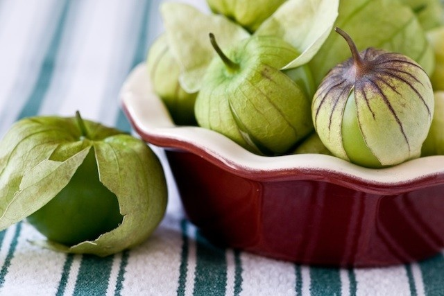 Great tomatillo recipe: 2 tomatillos, 1 avocado, 1/4 cup of sour cream, 1 clove of garlic, 1 jalapeno (seeded), handful of chopped cilantro. Stick it in the food processor until smooth. Delicious for a dip or to go with fish tacos!