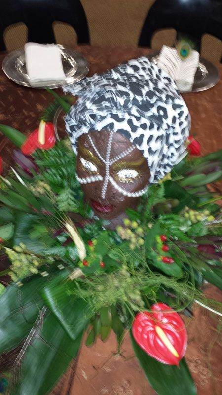 Xhosa themed centerpiece.  We painted a polystyrene head with the traditional Xhosa white dots and placed it amongst grasses and greenery with a few red anthiriums