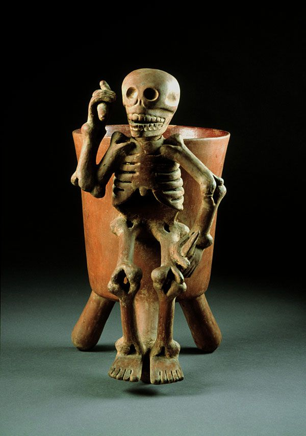 Its death-related motif may bespeak the funerary use of this vessel, found in one of the royal tombs of Zaachila. The figure holds objects in both his hands. Some scholars have interpreted these objects as weapons.