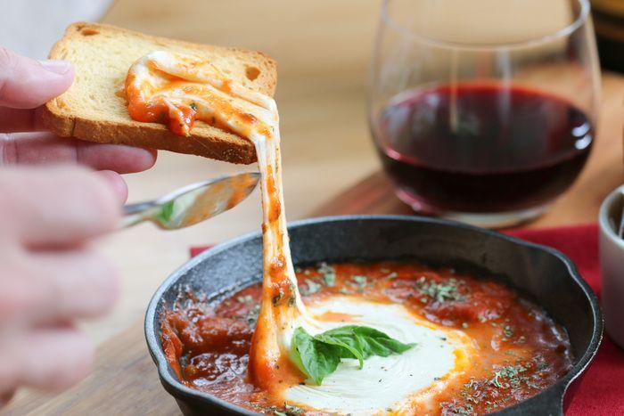 【ベイクドモツァレラトマト】 材料:マリナーラソース1カップ、モツァレラボール1/2個、生バジル、トースト(お好みで)  作り方:①耐熱皿にモツァレラボールをカットした面を下にして置き、マリナーラのパスタソースを周りに注ぎます。②オーブンで約200℃で約15-20分、チーズが溶けてソースがぐつぐつするまで焼きます。③オーブンから取り出してフレッシュバジルの葉を飾り、トーストを添えたら出来上がり。