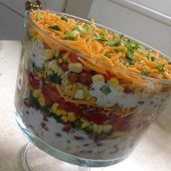 This layered salad is made with green chile cornbread, pinto beans, peppers, corn, bacon bits, tomatoes, and cheese. It's then chilled for two hours to allow the flavors to blend.