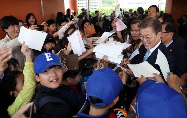 지난달 15일 서울 양천구 은정초등학교 어린이들이 '미세먼지 바로 알기 교실' 행사를 마치고 학교를 나서는 문 대통령을 향해 사인공세를 펴고 있다./청와대사진기자단