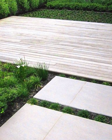 A Courtyard entrance garden with timber decking and wide tiled paving and lots of fresh green planting