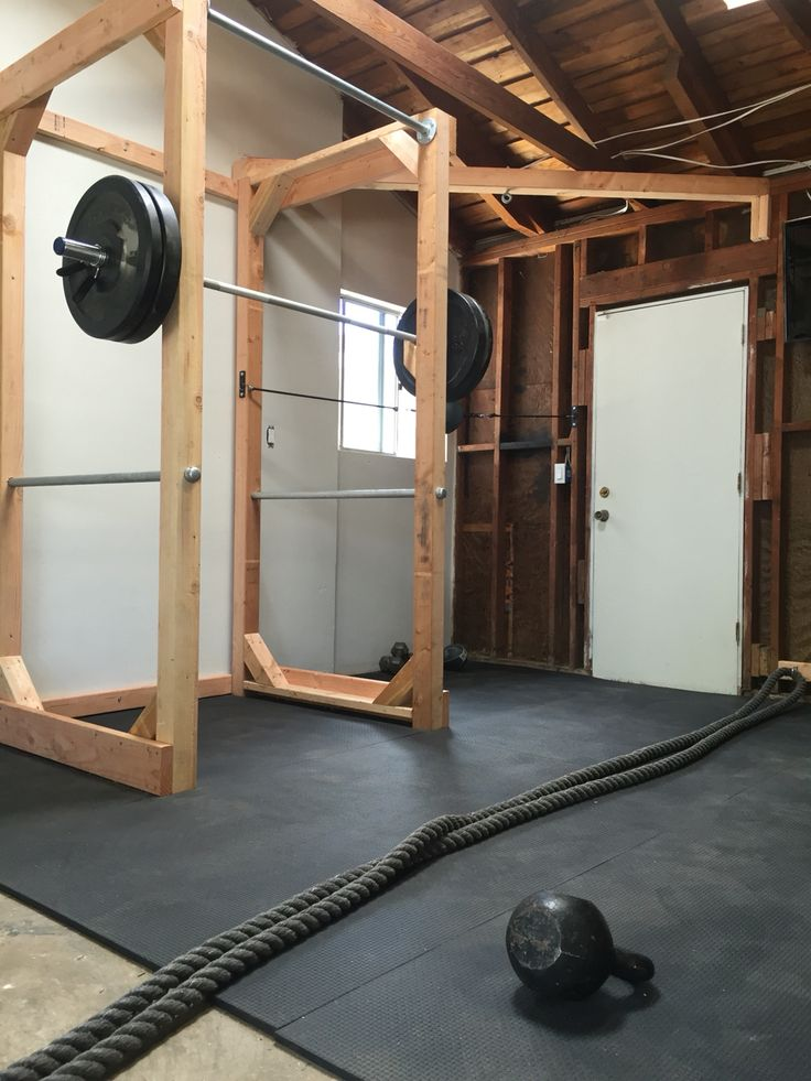 DIY home gym. Power rack built with lumber: 4x4s, 2x4s, 6x2s and 3 ft steel pipes for pull up bar and bar catch. Flooring: 100lb 4x6 recycled rubber mats  Built by: Grant Plummer Instagram: @heartandgrain  Follow him for incredible woodworking creations!!