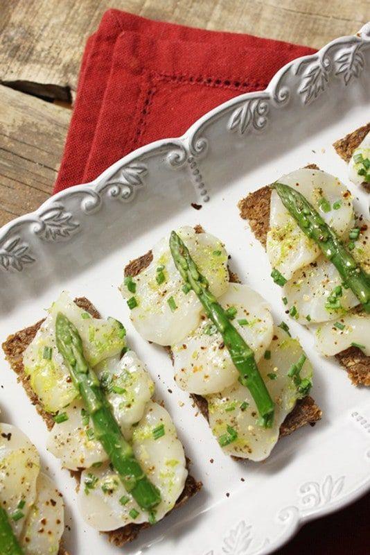 1. Snij de sint-jakobsnootjes met een scherp mes in fijne schijfjes (± 2 mm). Leg ze in een schotel. 2. Rasp de zeste van de limoenen en pers ze. 3. Giet het limoensap over de sint-jakobsnootjes en strooi de zeste erover. 4. Rasp de gember en voeg toe. 5.