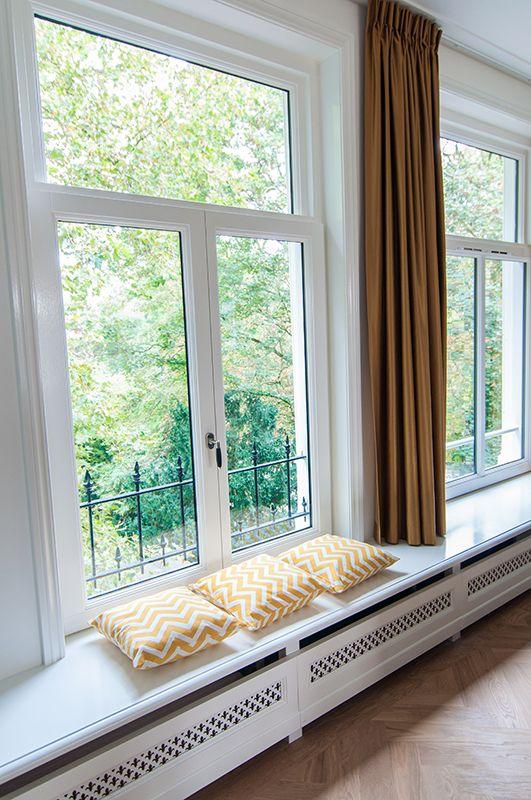 De woonkamer van het bovenhuis heeft een brede vensterbank waarin je kunt zitten // Renovatie herenhuis Vondelbuurt // Lumen Architectuur