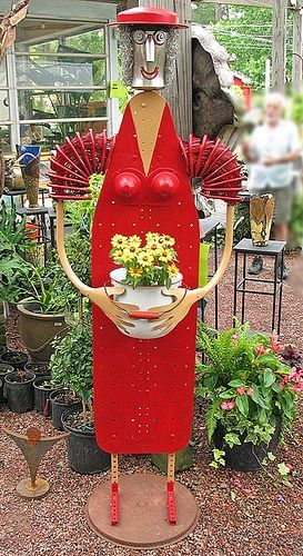 """Ironing-Board Lady 6' 3"""" tall. Made from an ironing board, other found objects, hardware, paint and flowers."""