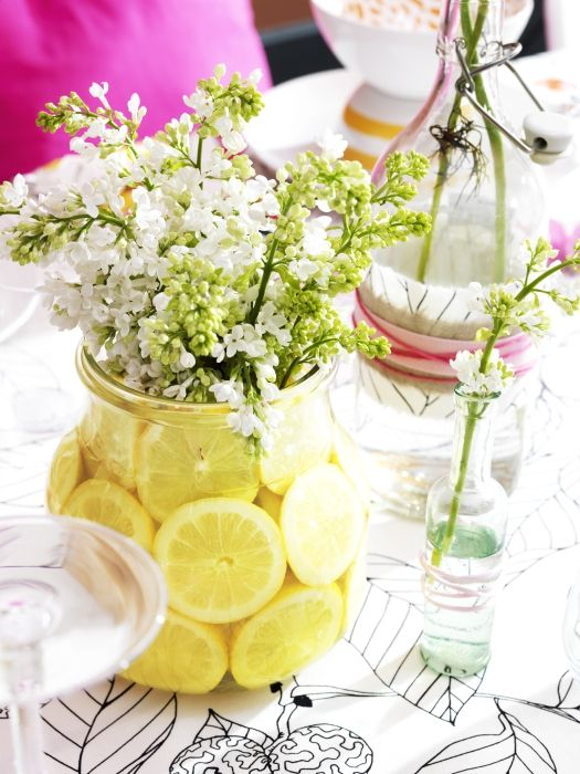 Fill clear glass ENSIDIG vases from IKEA with sliced lemons and sprays of flowers for fresh and inexpensive table decorations.