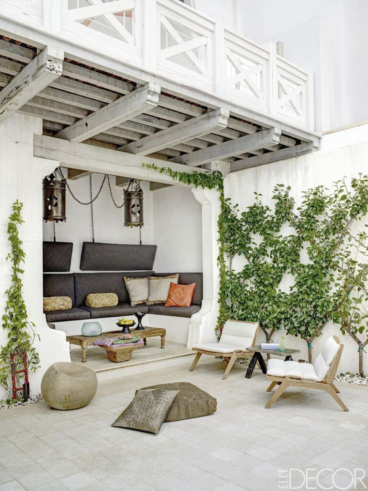 The courtyard holds teak lounge chairs by Henry Hall Designs, a custom-made banquette with cushions in a Perennials fabric, and antique Spanish lanterns found in Belgium.   - ELLEDecor.com