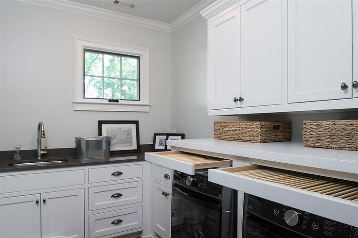 Black and white laundry room features white shaker cabinets paired with charcoal gray quartz countertops fitted with a curved stainless steel sink and a satin nickel gooseneck faucet.