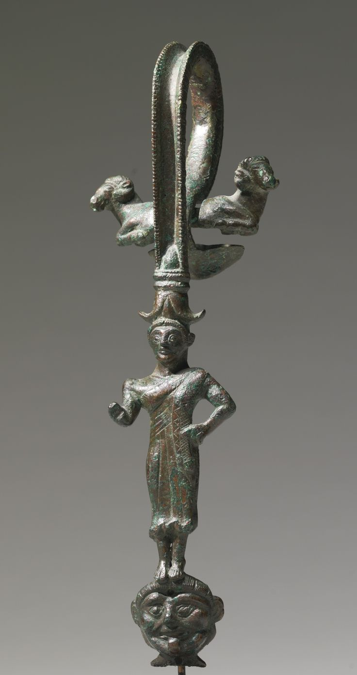 AN ETRUSCAN BRONZE HANDLE, CIRCA EARLY 5TH CENTURY B.C. in the form of a youth standing on a gorgoneion mask and wearing a partially crosshatched pleated garment falling from the left shoulder, the high concave handle chased on each side with an ovolo kymation, and terminating at the top in the forequarters of two rams back-to-back, attached by a rivet, and at the base in an inverted lotus flower.