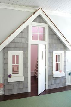 This quaint indoor playhouse from Myefski Architects features a cute facade nearly flush with a wall to keep the playroom contained. A white fence, cedar-style shingles, and window boxes for tucking in faux flowers add to the interior structure's charm. A non-locking front door, windows, and transom keep little ones under adult supervision.