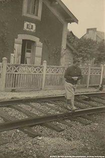 6| Photographie de Mme Lévêque traversant la voie ferrée devant sa maison au PN 13 de Reims, vers 1950. En tant que garde-barrière, Mme Lévêque travaillait 6 jours par semaine, de 6h du matin à 9h du soir, et avait un repos tous les 4 ans pour les fêtes de fin d'année. Les conditions de travail à Reims, où elle fut mutée en 1942, étaient très différentes de celles de Nuisement-sur-Coole [Marne]. Le trafic au passage à niveau 13 de Reims était également bien supérieur.