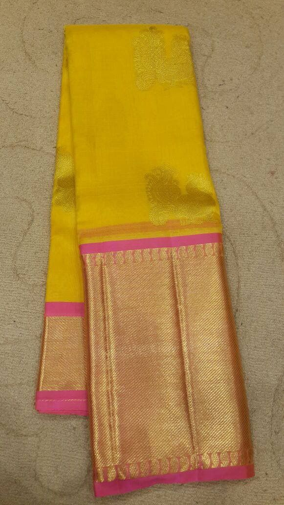 Beautiful yellow and good kanchipuram silk saree with thin pink contrast. Would go perfect with a pink brocade blouse.