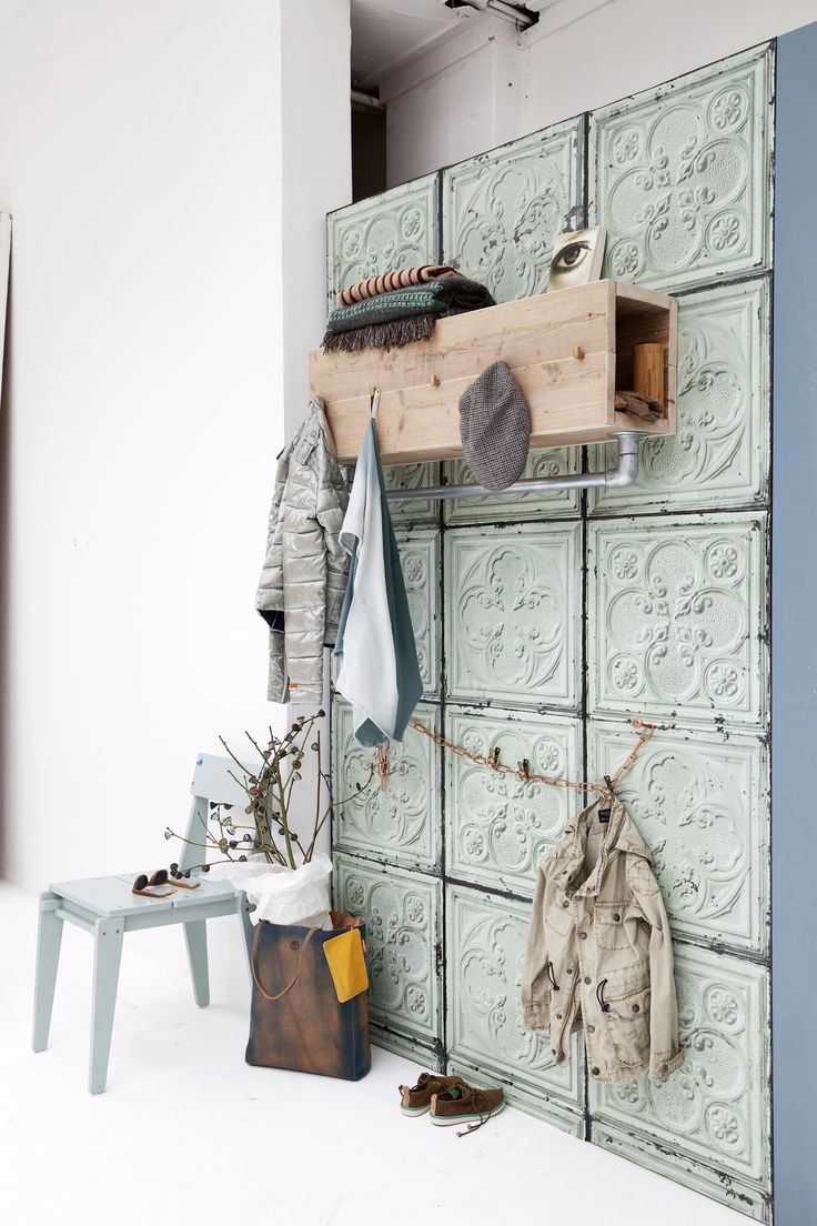 DIY coat rack of scaffolding tubes and wood on rustic metal wall panels