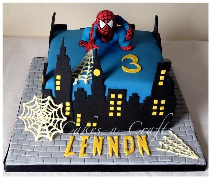 """8"""" spiderman cake with hand cut buildings and sugar model. the webs are made from chocolate and his name is handcut using the spiderman font"""