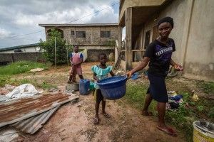 Young girls wash with their hands in Lagos