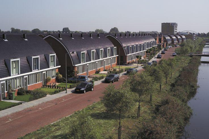 Eensgezinswoningen in Leidschenveen een hellend dak en een verticale gevelbekleding gerealiseerd met de Tuilde du Nord 44 natuurrood. Moderne architectuur met dakpannen.