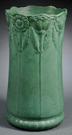A Weller Pottery umbrella stand, Zanesville, Ohio, decorated around the rim with raised flowers on trailing stems, Bedford green matte glaze