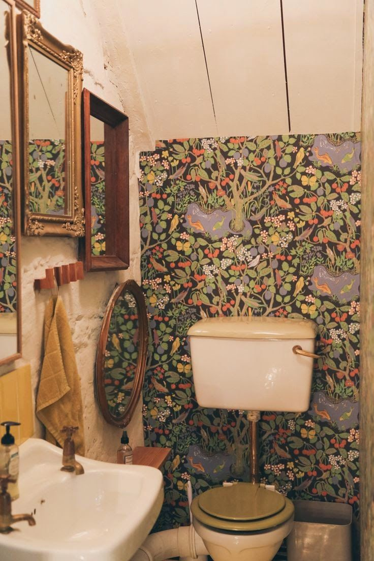 Gypsy print wallpaper in this beautiful, tiny bathroom, complete with vintage mirrors #interiors #wallpaper