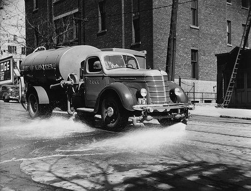 Un camion-citerne à eau faisant le nettoyage des rues, 1948