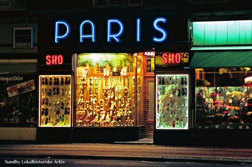 Denne gamle skoforretning med de veludstyrede vinduer og det smukke neonlys fandtes på Amagerbrogade ved Holmbladsgade til omkring 1995, hvor den blev afløst af en modeforretning. Det lader til at neonlysene på Amagerbrogades forretninger på det seneste har fået en vis renæssance, f. eks. bageren ved Englandsvej.  Foto Flemming Lamberth, 1992.
