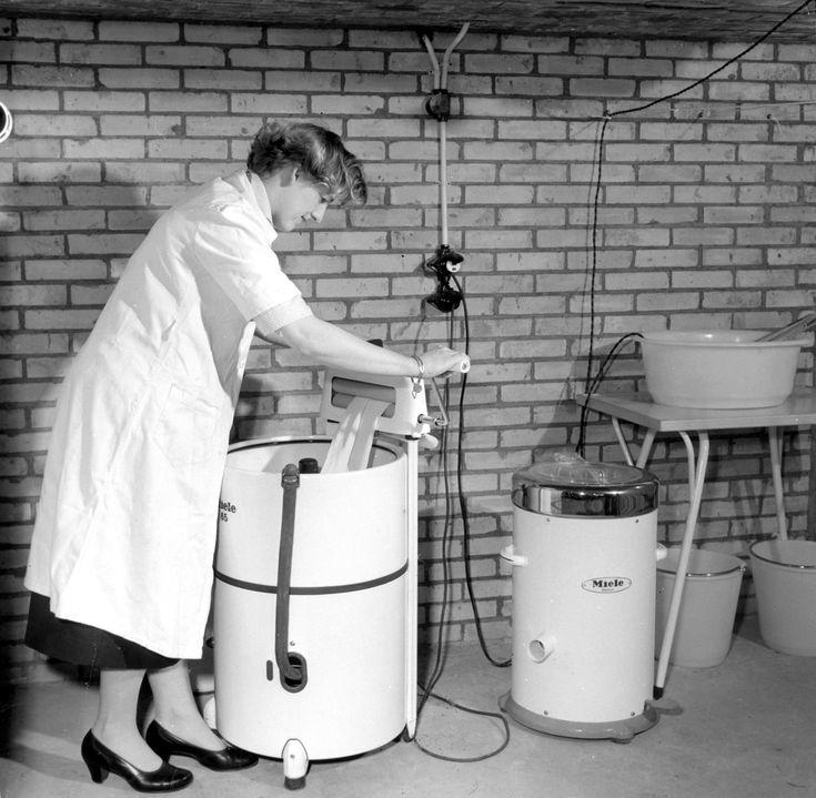 Wasdag in de bijkeuken. Ze haalt de was door de wringer bovenop haar Miele langzaamwasser, ernaast een Miele centrifuge. Februari 1957.