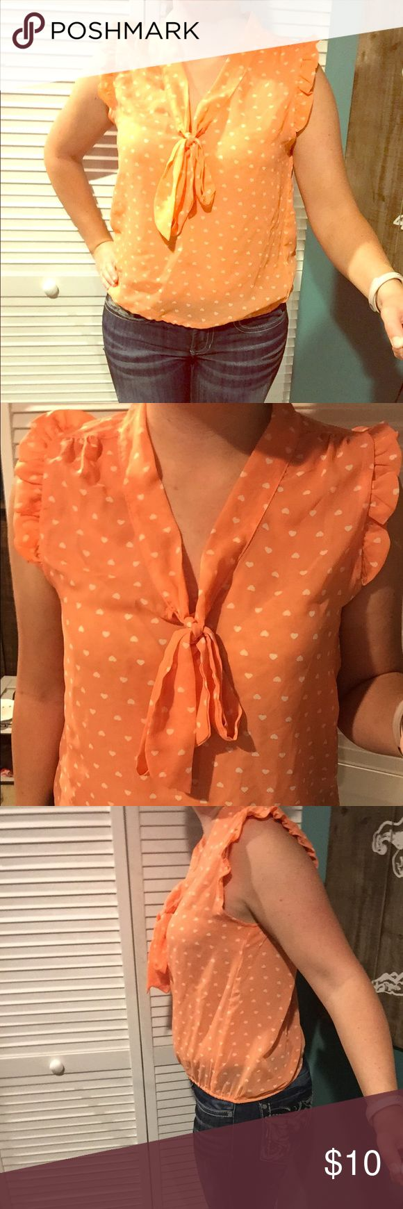 Orange blouse Orange sleeveless blouse with small white hearts. Ruffles around arm holes and small tie at the neck hemline. Elastic band at bottom hemline. I suggest wearing a tank or cami underneath. Worn several times but no marks and is clean. Eyelash Couture Tops Blouses