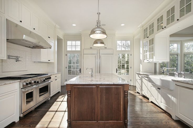 Large and bright white kitchen with windows along two walls.  Some cabinets are suspended from the ceiling with glass faced design.  Brown island runs down the center of the space.