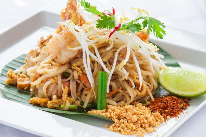 Pad Thai, tagliatelline di riso saltate con verdure, uovo, salsa di soya, gamberi o pollo.