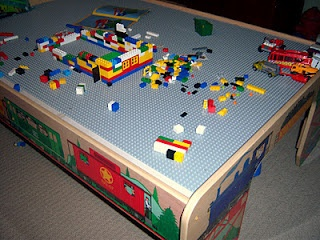 Lego table made from train table. I did something very similar to this with a thomas train table. The table top still flips over, so it can be used for cars or play doh or whatever. I use Rubbermaid bins to hold the pieces since it has no built in storage.