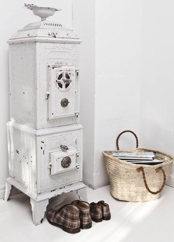 Vanhan rautakamiinan Olof on saanut perintönä. Tällä hetkellä kamiina on pelkästään koriste, mutta tulevaisuudessa se on tarkoitus laittaa kuntoon. Kamiinan kanssa kaveeraavat Olofin ja Oliverin Reino-tossut. Oikealla on Tine K Homen olkikassi, joka on täynnä sisustuslehtiä.