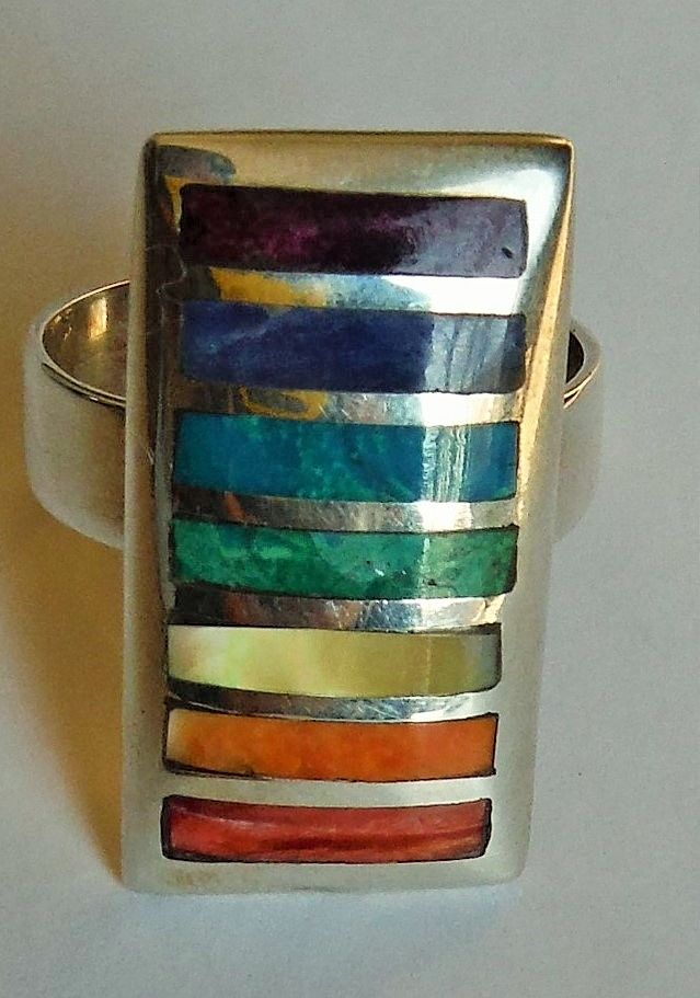 Beautiful cocktail ring made with Peruvian silver and inlaid stones like Sodalite, Chrysocolla,Mother of Pearl,Lapis Lazuli, Amethyst and Coral. https://www.facebook.com/pages/Peruvian-Qulqi/118631258281479?ref=hl