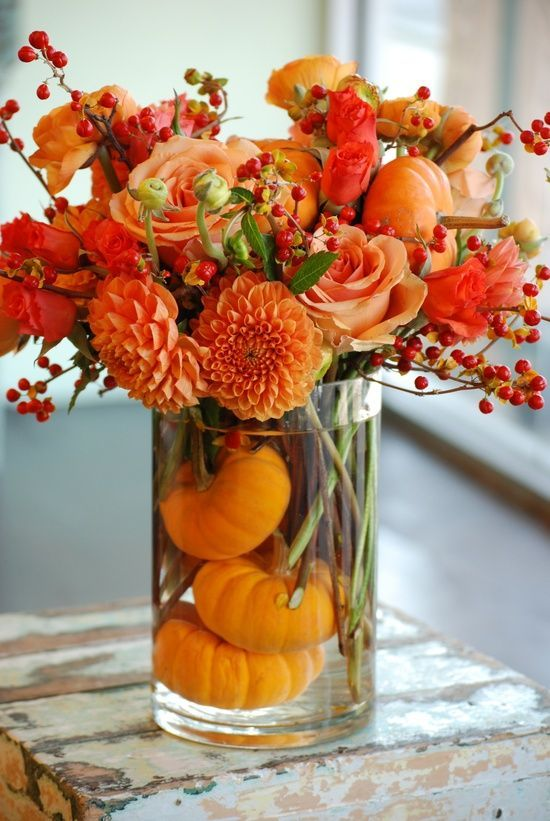 Stunning Fall Floral Centerpiece! Fall is all about bright colors in orange and yellow, and this centerpiece is made up of a glass jar filled with small sized pumpkins and fresh cut flowers like dahlia and roses in a bunch that top the vase as a beautiful centerpiece.