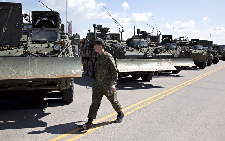 Military vehicles lines the street as troops are briefed before heading in to the flood zone in High River, Alta. on Saturday June 22, 2013 after the Highwood River overflowed its banks.