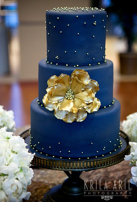 Brides.com: 22 Wedding Cakes for Dark, Modern Color Palettes. A Midnight Blue and Gold Wedding Cake. Doesn't this stunning, dark blue Amy Cakes confection look made for a glamorous wedding with Bollywood flair? The brushed gold flower is a knockout addition.   See more blue wedding cakes.