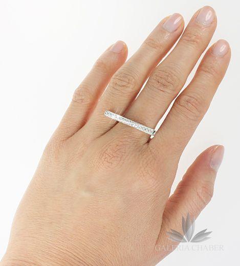 Pierścionek w nietypowym kształtcie, wysadzany cyrkoniami o szlifie brylantowym, wykonany ze srebra próby 925, rodowany. Oprawa wzbogacona dodatkowymi kamieniami do okoła całej oprawy, również z boków. Wyrób w rozmiarze 17. Wzór o szerokości około 2,7 cm.