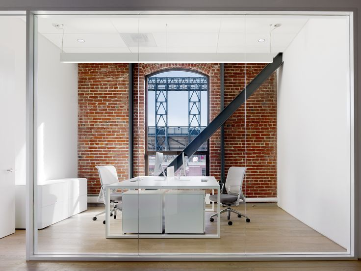Beautiful office with red brick wall and a giant window. #office #brickwall #modern