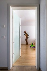 Weißlacktür als Zugang zum Wohnbereich. Mit dem Glasanteil und den Edelstahllisenen wirkt dieses Element top modern und doch zeitlos.