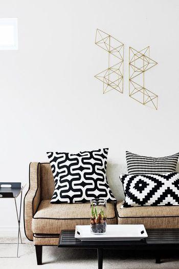 壁面に飾り付けたヒンメリと、幾何学模様のクッションカバーが印象的な、北欧モダンのコーディネート。  室内がどこかボヤケた印象なら、幾何学模様で引き締めて。