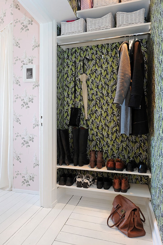 great example of open storage. Shelves are built in for shoes, and a rack is built in to hang clothing. In this space, the walls are covered in a beautiful complementing dark green floral wallpaper.