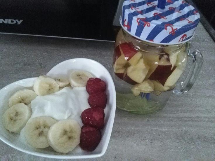 Breakfast, white yogurt and water with fruits.