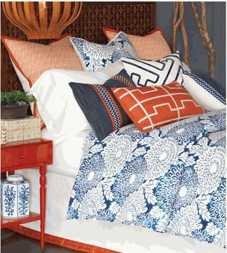 Caribbean luxury bedding featuring Asian inspired floral print: rich blue on white and bright orange accents, geometric appliqué details.