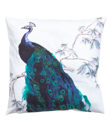 Cotton cushion cover with a printed motif at front, solid-color back, and concealed zip.