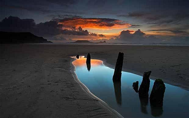 The sun sets at  Rhossili Bay, Wales