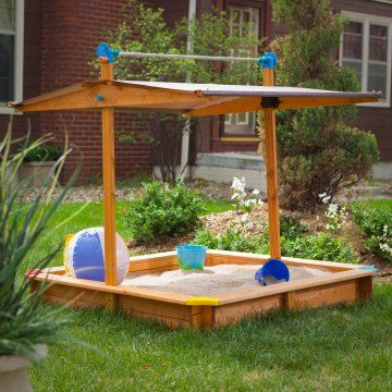 Wooden sandbox with a sun shade that cranks down to cover the sand when not in use.