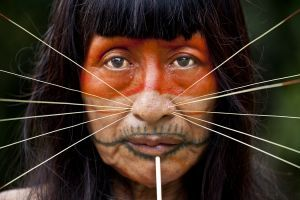 """An elder from the Matses tribe in Peru's Amazon jungle, wear the traditional whiskers and spike in her chin.  She has facial tattoos and paints achiote fruit onto her face.  Her tribe is often referred to as """"The Cat People"""".   Photographed by Alicia Fox as part of Portraits of The Disappearing Amazon project"""