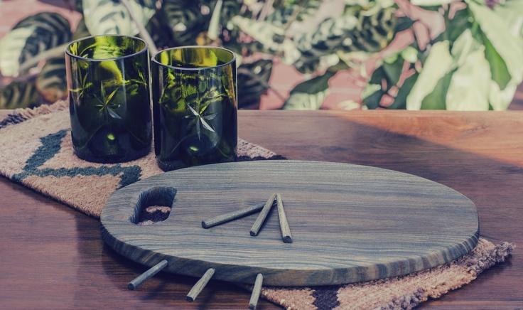 Vasos de vidrio fabricados a partir del corte y pulido de botellas de vino de vidrio descartadas. Tabla y pinchos de madera de palo santo. Camino de lana teñida con tintes naturales y tejida en telar. (Obra Inspiración Sustentable)
