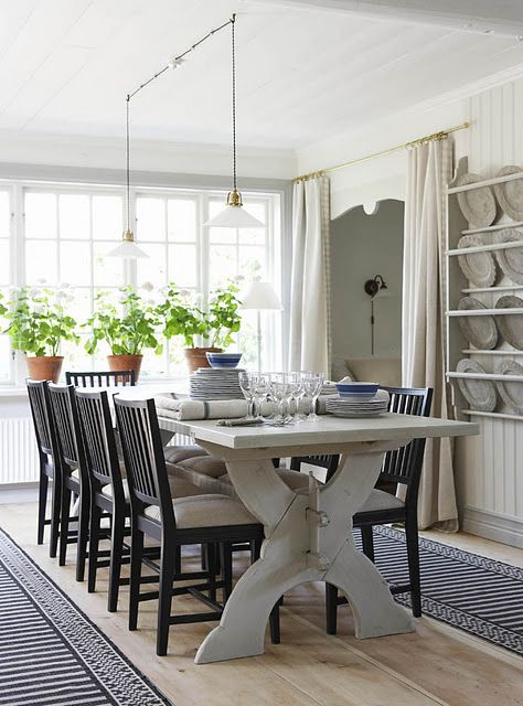 lovely dining room: lighting, windows, bead-board and plate rack.  but what is that behind the curtains?