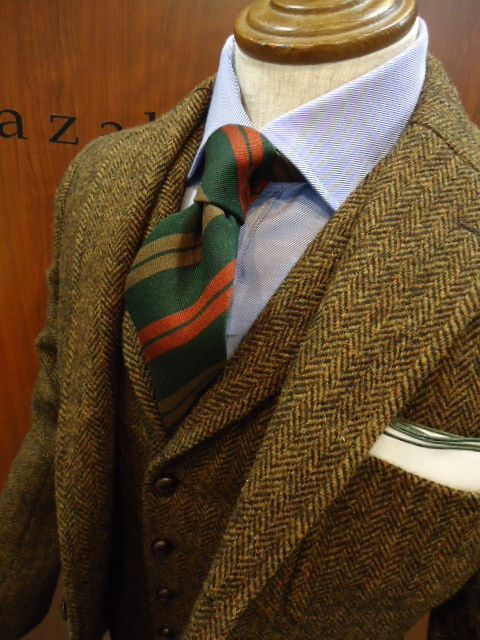 Tweed jacket, light blue shirt, green tie with gold and orange stripes